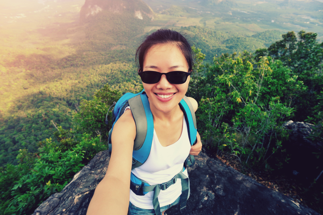 hiking woman taking photo with smart phone on mountain peak